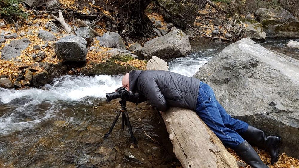 photographer bending over a log to take a picture of a river