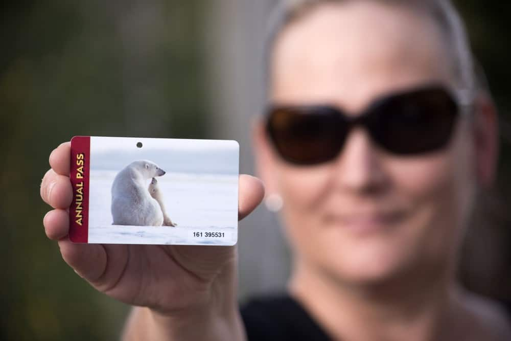 woman holding a US national parks pass card