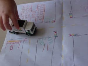 Toy car driving along a scene drawn on paper