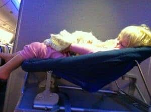 Toddler girl sleeping in a bulkhead row bassinet on an airplane