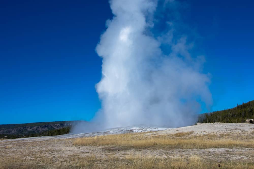 Old Faithful in the fall with steam at Yellowstone National Park