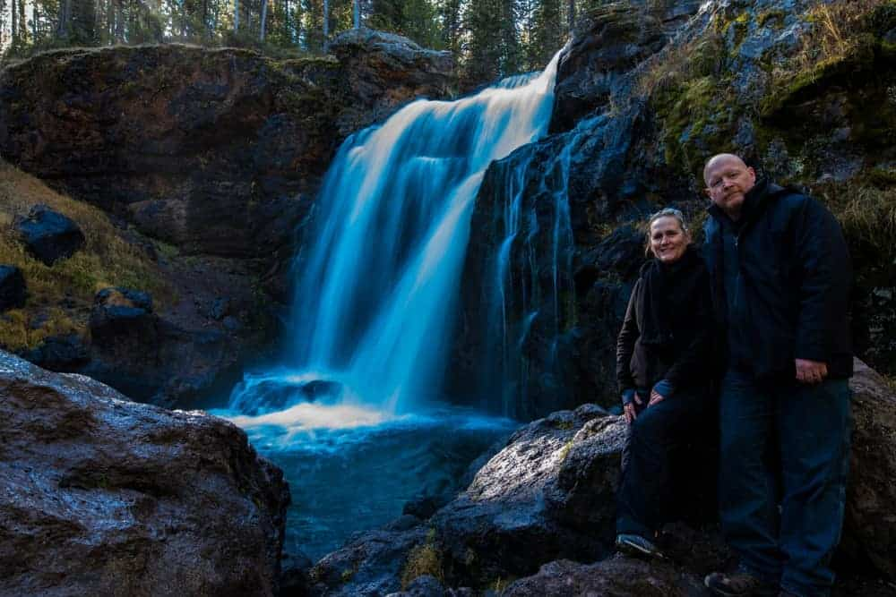 A man and woman standing by Moose Falls in Yellowstone National Park