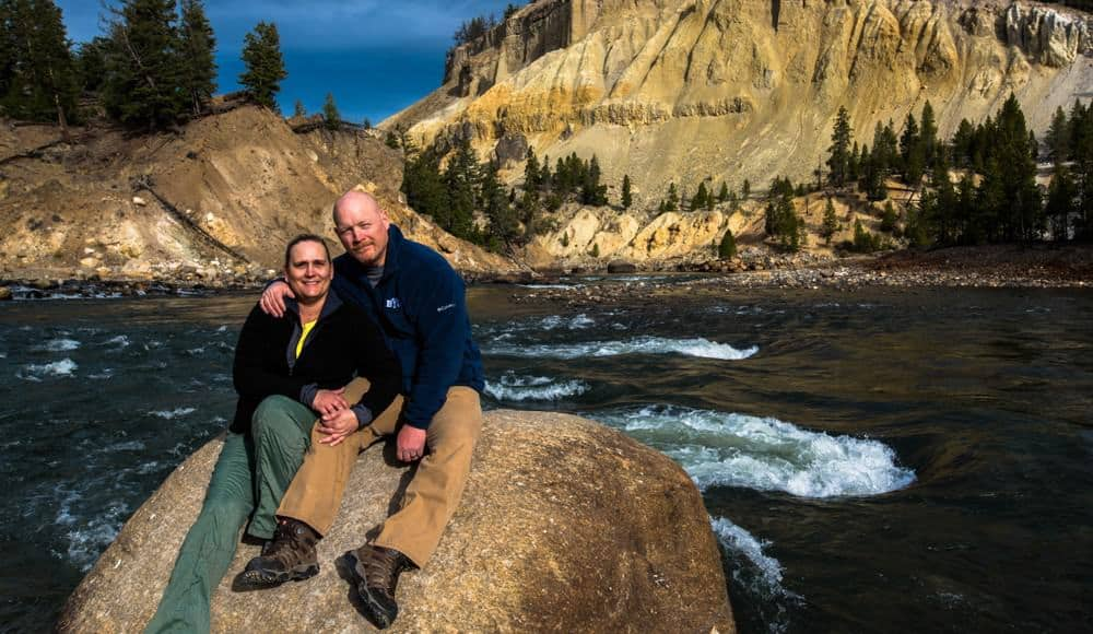 A man and woman on a large rock along the bank of the Yellowstone River