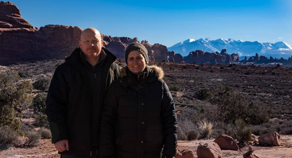 man and woman dressed in winter clothing during the winter at Arches National Park