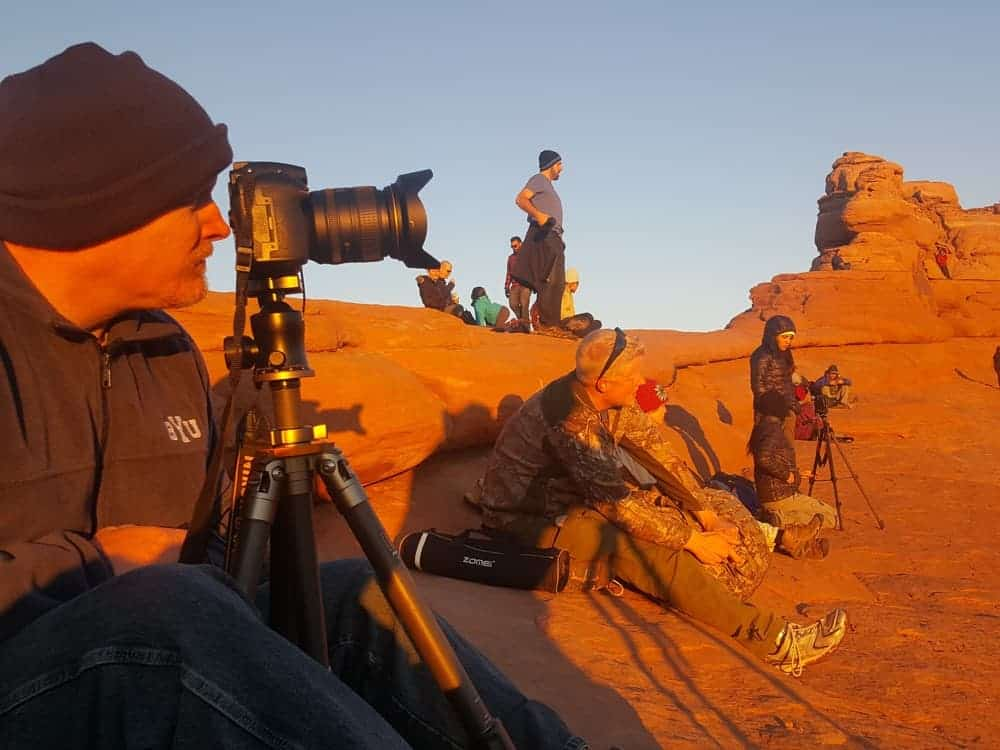 man photographing Delicate Arch during the winter at Arches National Park
