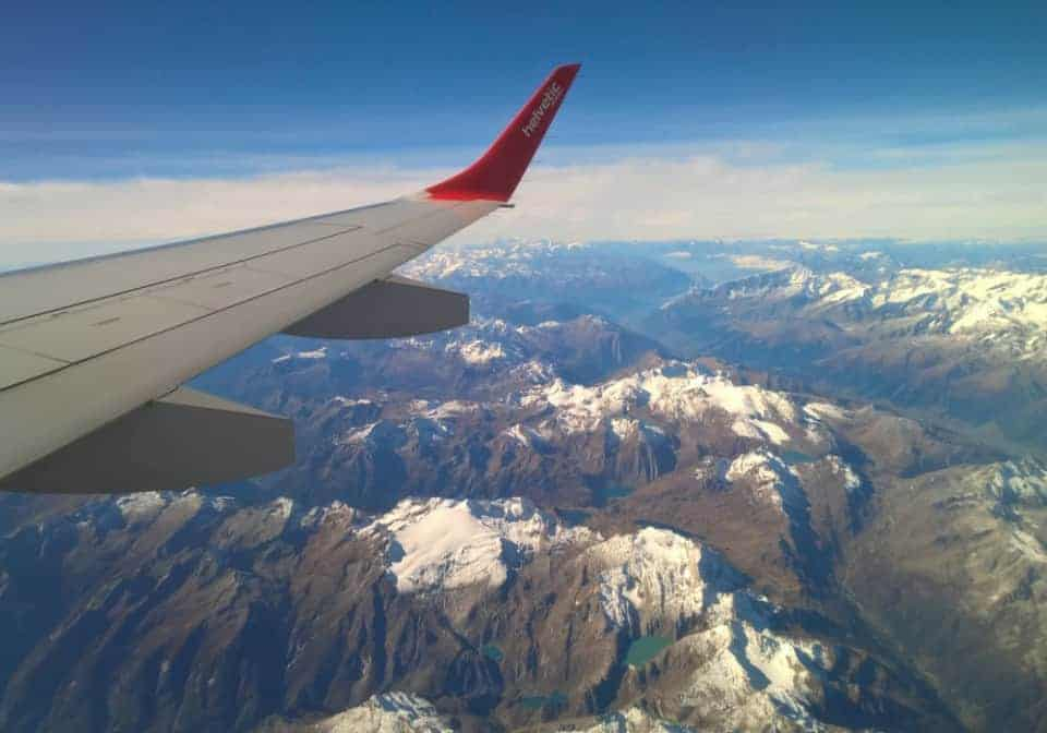 An airplane wing and snow-capped mountains viewed through the airplane window while in flight.