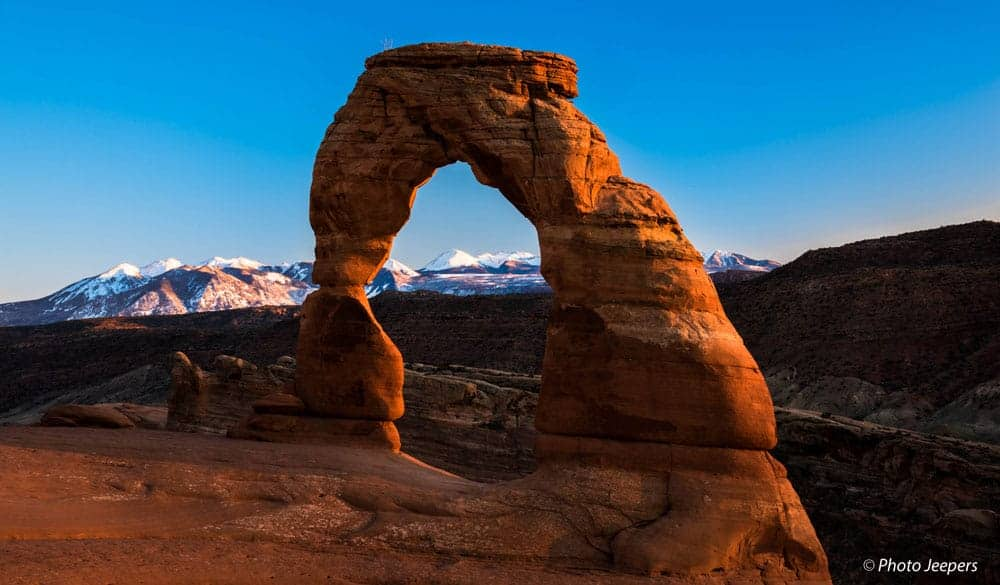 Delicate Arch with snow-capped mountains in the distance at Arches National Park, Utah - US National Park List: 25 Beautiful Parks to Visit