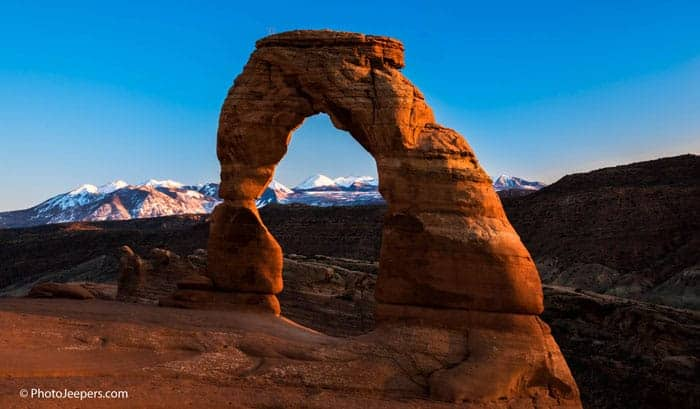 Arches National Park Photography - Delicate Arch at sunset with snowy mountains in the background