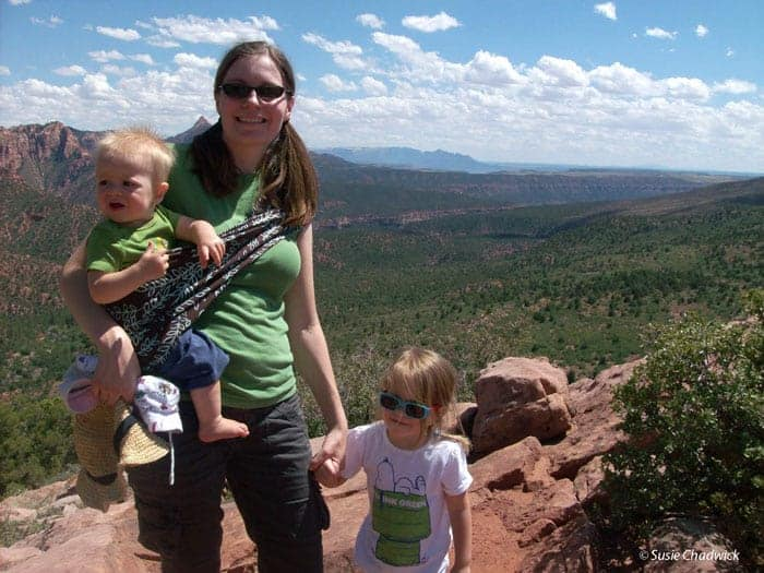 Hiking Gear List and Tips for Kids - Mom with baby in a sling carrier holding hands with a toddler girl