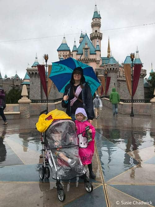 Mom, toddler girl and baby in the rain at Disneyland. Rain ponchos and umbrellas are a Disney Packing List item.