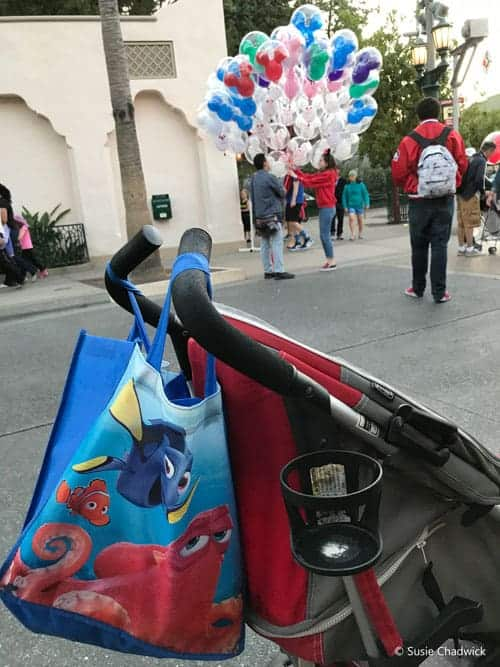 Stroller with a tote bag hanging on the handles at Disneyland.