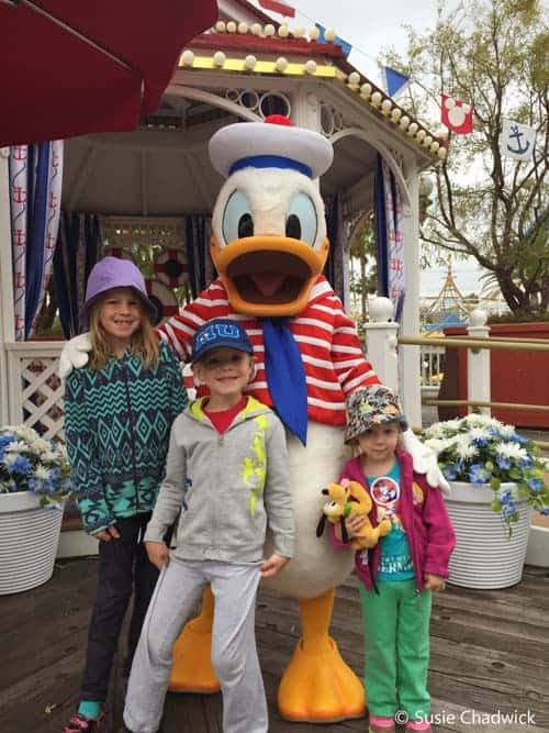 Three children with Donald Duck at Disneyland. They are all wearing a hat which is a Disney Packing List item.