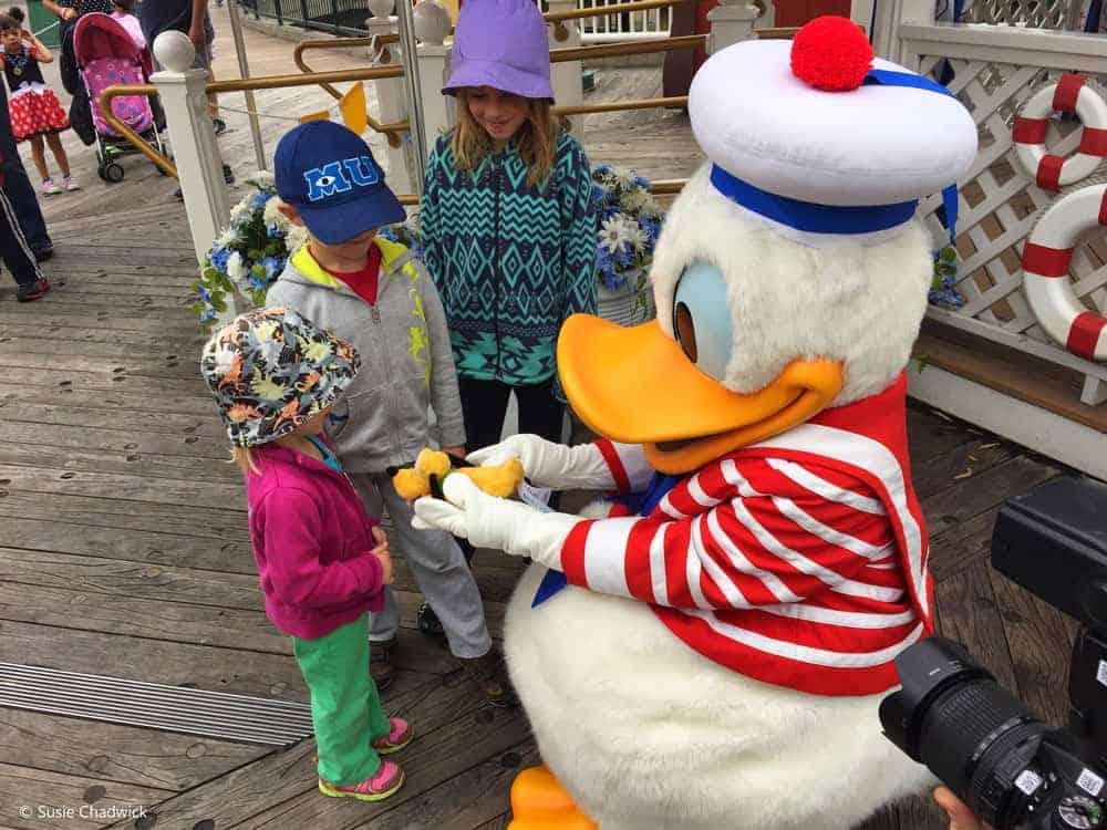 Three kids with Donald Duck signing an autograph book.