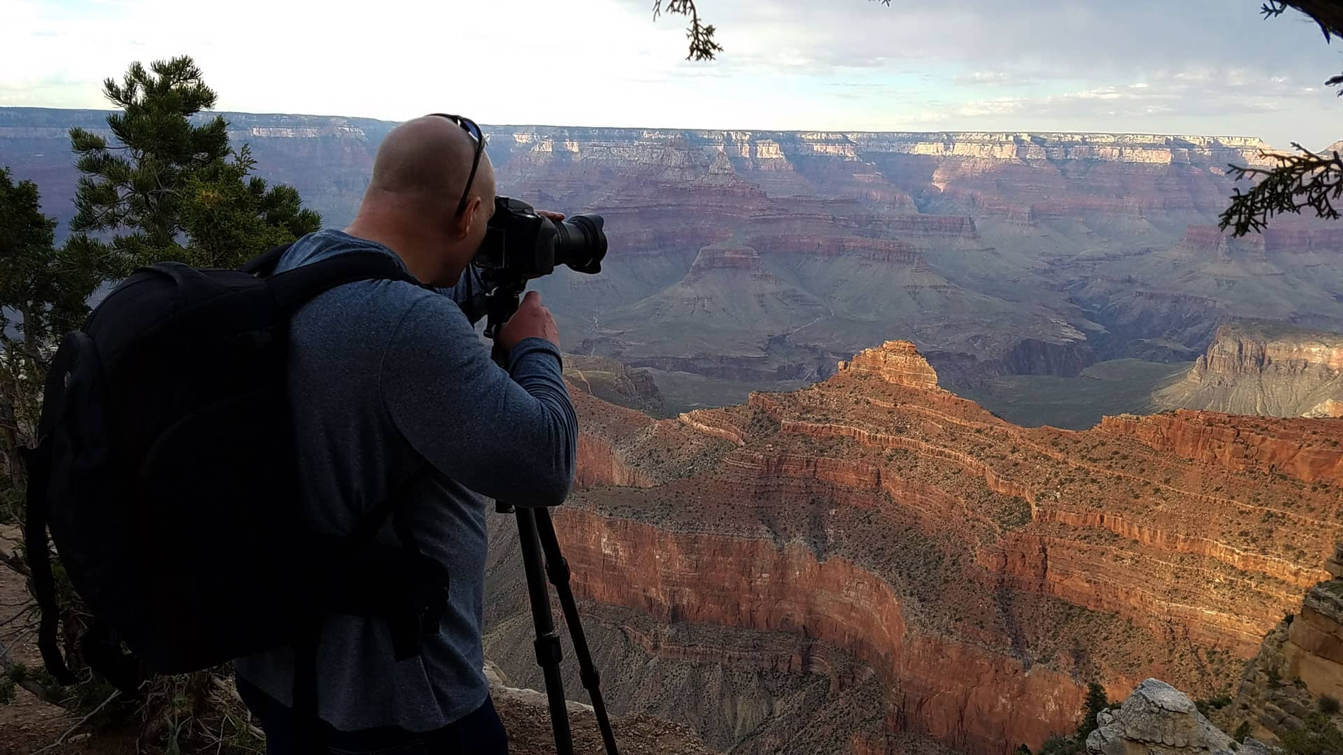 photographer with camera, tripod and backpack taking a picture of the Grand Canyon