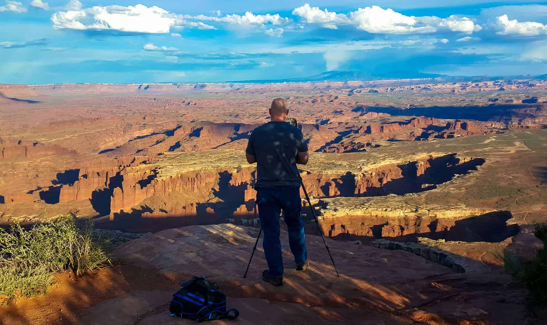 A photographer overlooking Canyonlands National Park at Grand View point taking a photo with a tripod.