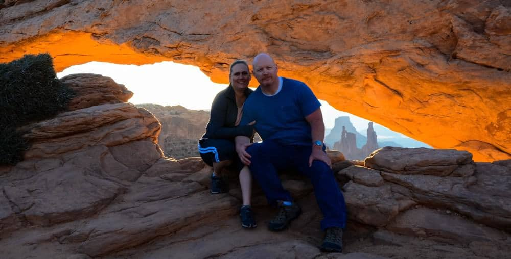 Man and woman at Mesa Arch in Canyonlands National Park, Utah at sunrise.