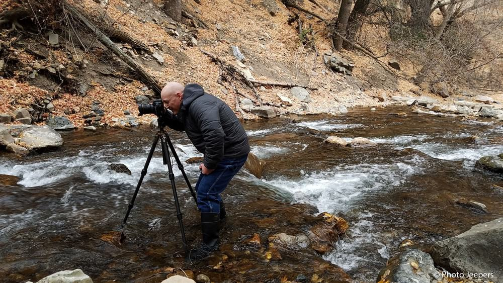 A photographer standing in the middle of a river taking a photo with his tripod.