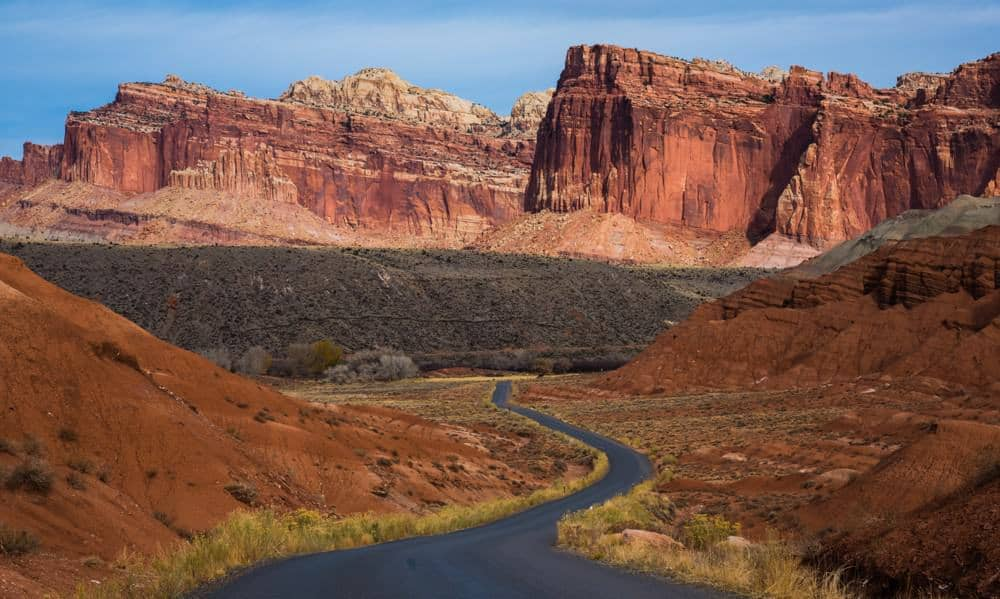 Winding road leading toward the red rock mountains at Capitol Reef National Park, Utah