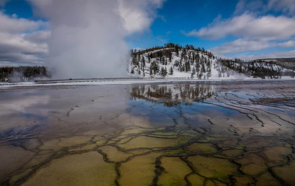 Reflection of geyser steam and snow-covered mountain in the shallow water around the Grand Prismatic geyser at Yellowstone National Park in the winter.