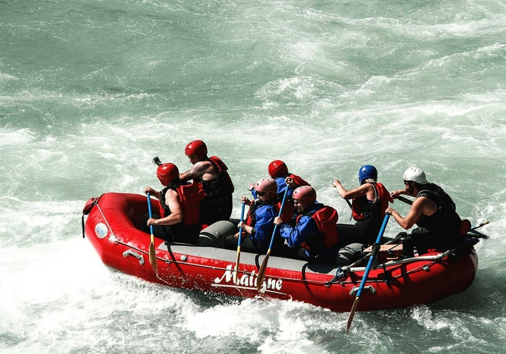 Red raft going down rapids on a river - white water river rafting