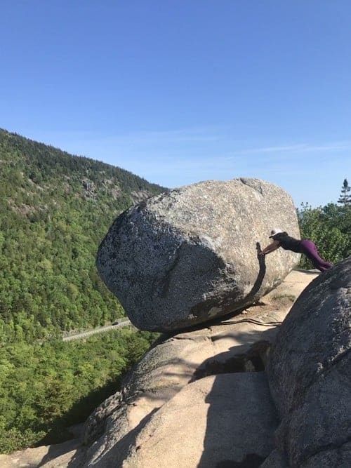 Woman pushing rock along Bubble Rock Trail at Acadia National Park - US National Park List: 25 Beautiful Parks to Visit