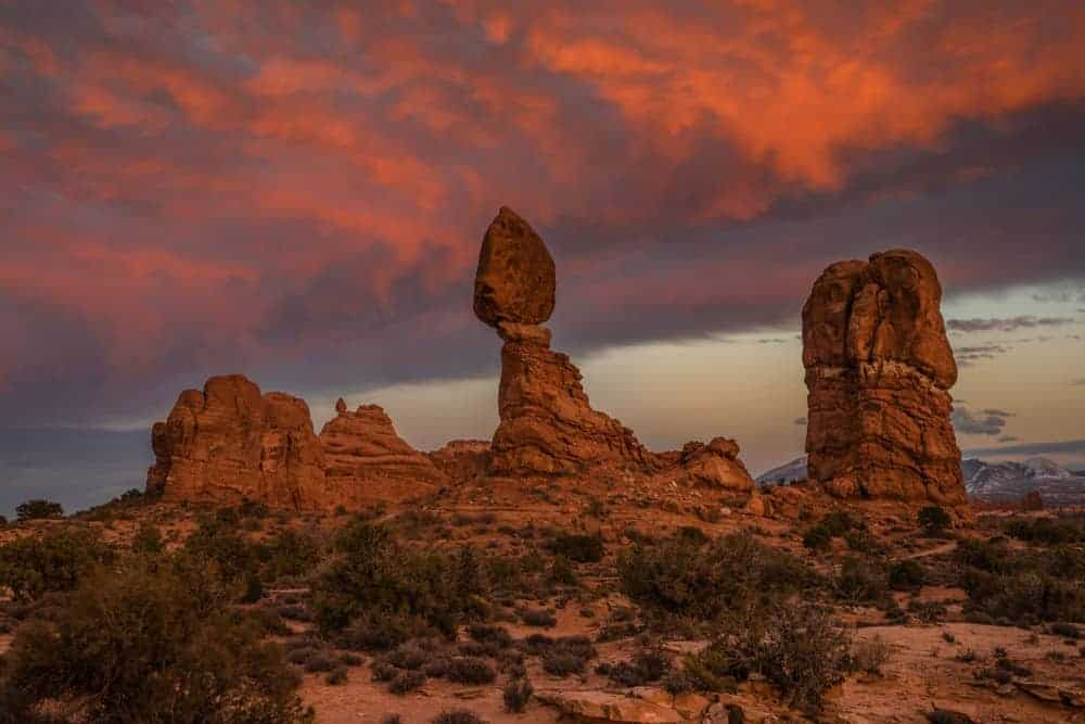 Balanced Rock at Arches National Park, Utah at sunset with colorful clouds in the sky