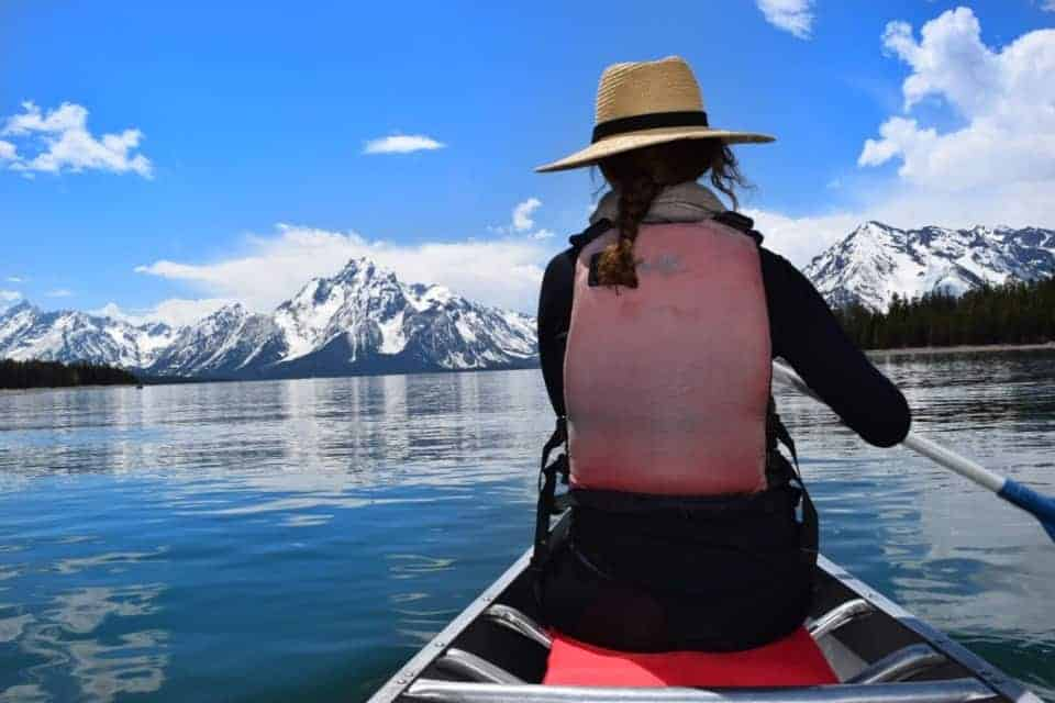 Woman in a canoe on Jackson Lake at Grand Teton National Park - US National Park List: 25 Beautiful Parks to Visit
