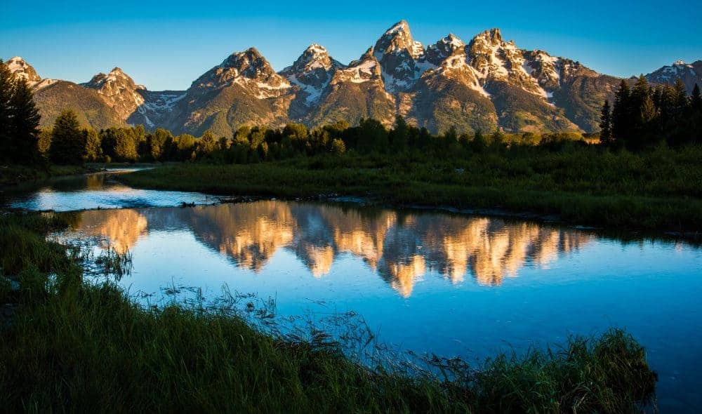 Sunrise Photography: Tips to Get Beautiful Sunrise Photos - Grand Teton National Park mountains reflected in the snake river at sunrise