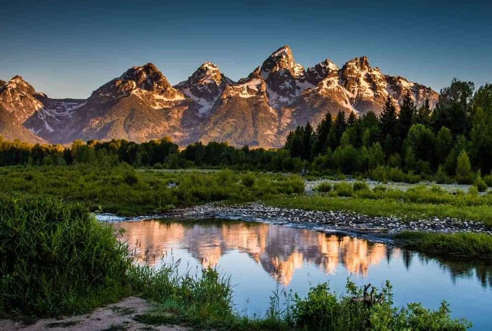 Reflection of the Tetons illuminated with morning sunlight.