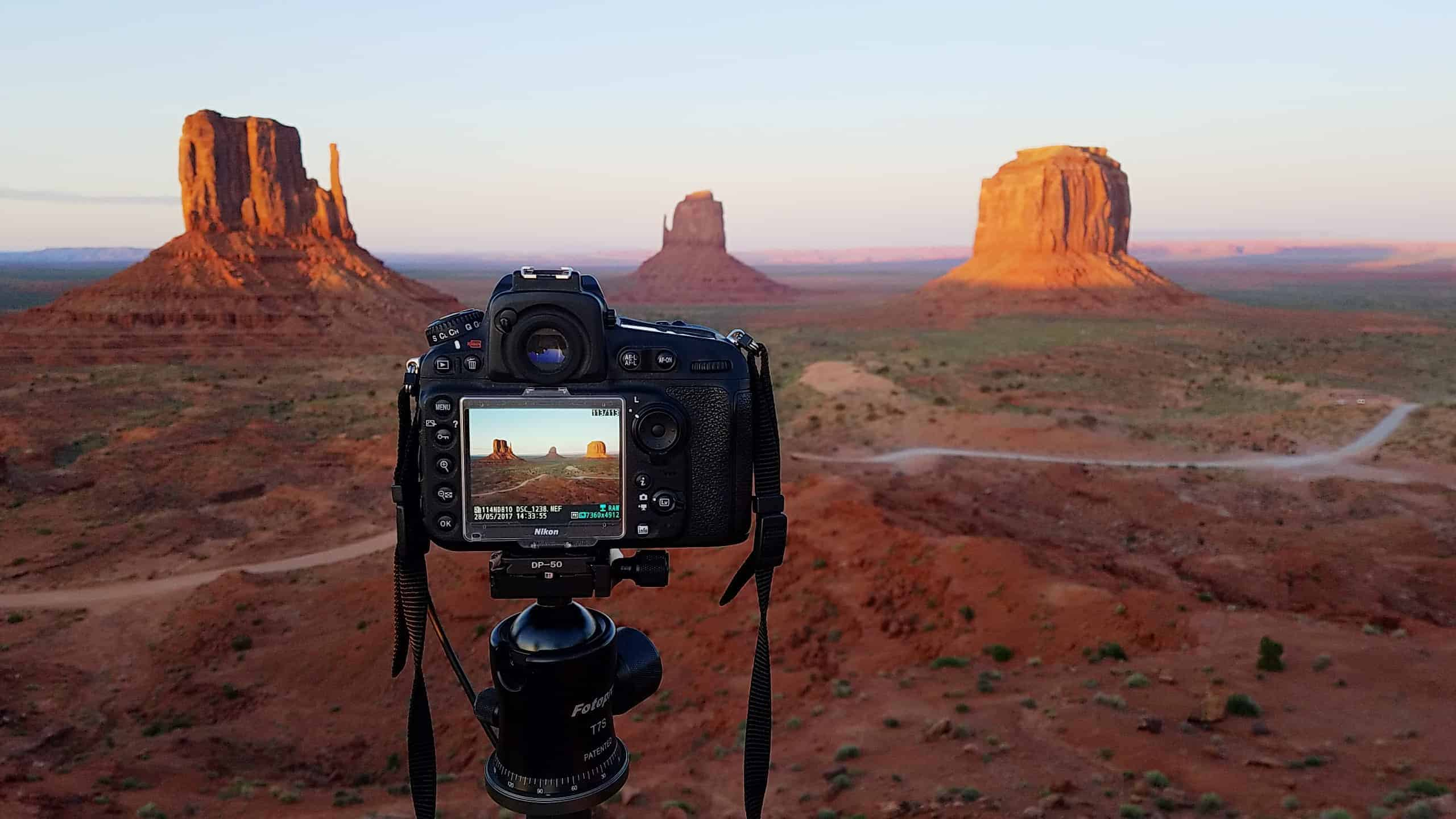 Camera on a tripod photographing Monument Valley at sunset