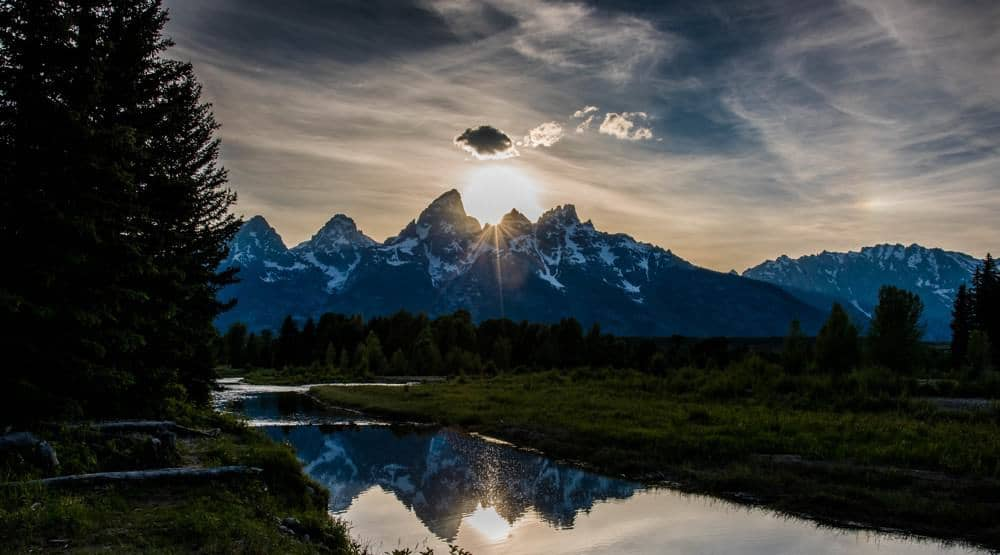 The sun setting behind the Teton mountains at Grand Teton National Park, and the scene reflected in the river