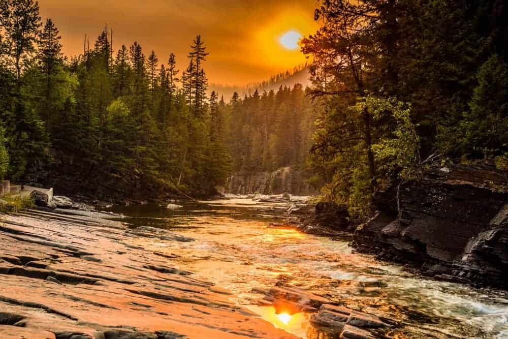The sunset along the river at Glacier National Park with the air filled with smoke during a wildfire