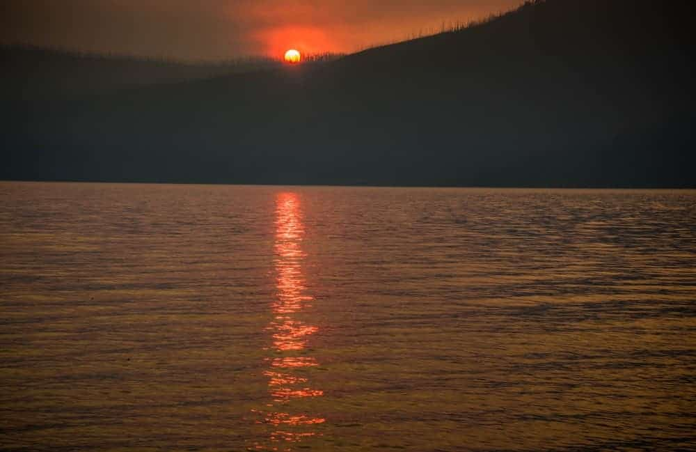 Sunset at McDonald Lake in Glacier National Park - the sun is red due to smoke in the air from a wildfire