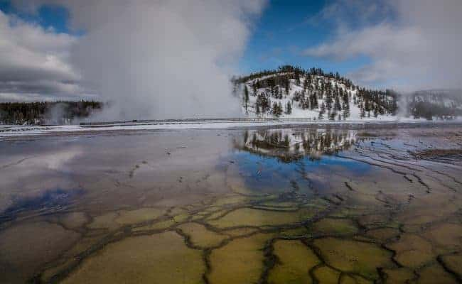 Geyser reflection and steam in the winter at Yellowstone National Park