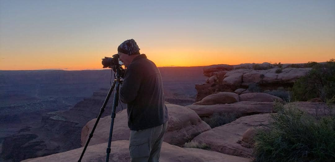 Photographer with tripod at Canyonlands at sunset