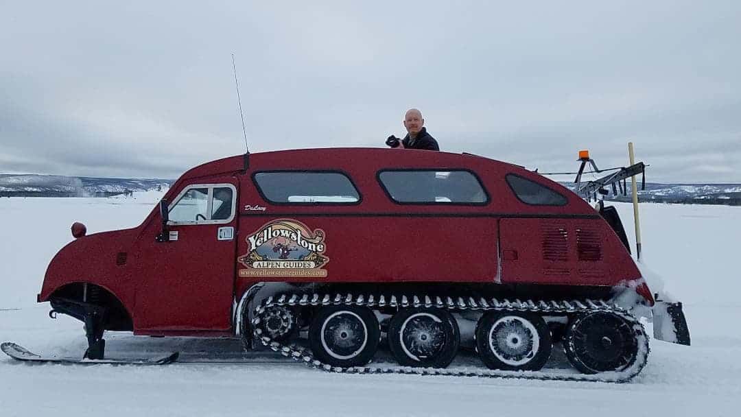 Man sticking head out of bombardier snowcoach at Yellowstone in the winter