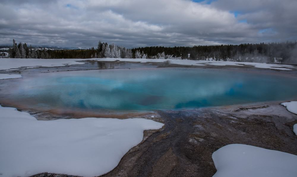 Views of hot pools against white snow when you visit Yellowstone in the winter.