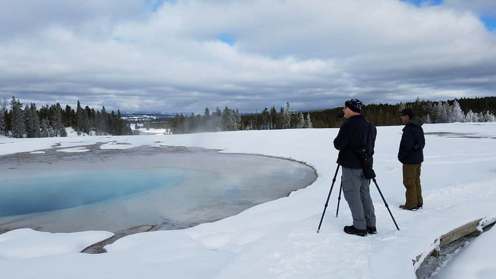 Photographer and man at blue hot pool at Yellowstone in the winter