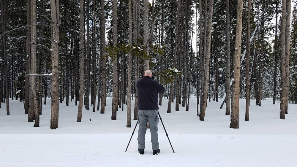Photographer taking pictures of a snowy landscape at Yellowstone in the winter