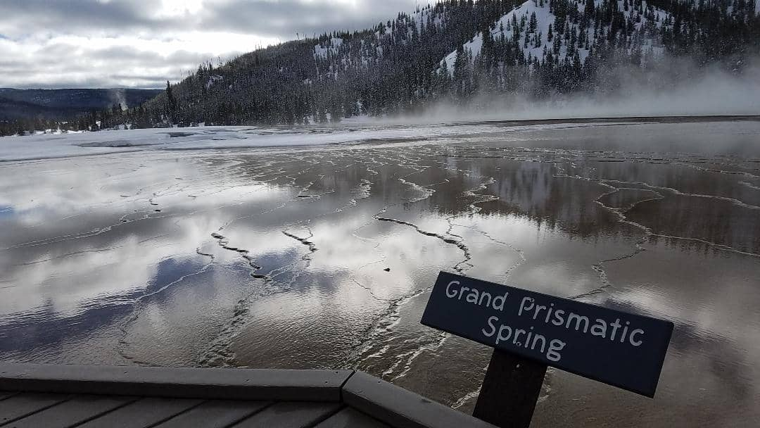 Reflection of snowy mountain and steam in water at Grand Prismatic Spring at Yellowstone in the winter
