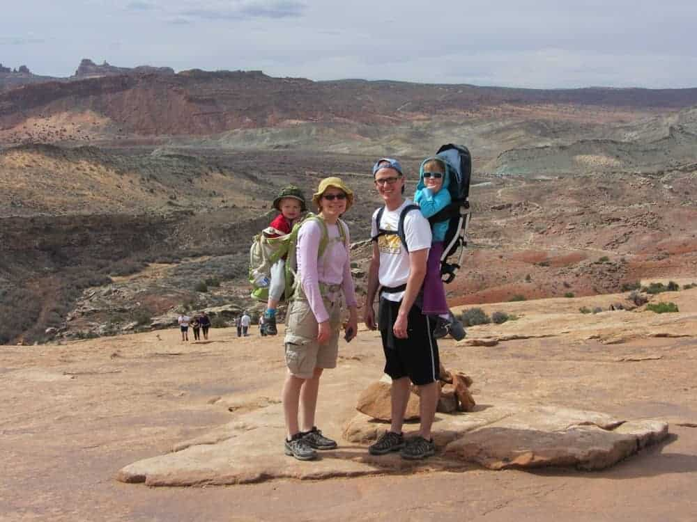 Mom and Dad on a hike in Arches National Park with kids in carriers
