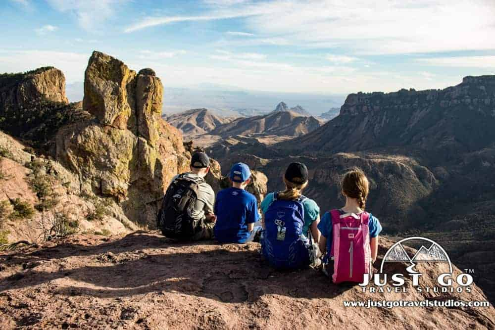 Four kids with backpack sitting at an overlook at Big Bend National Park: National Parks with kids