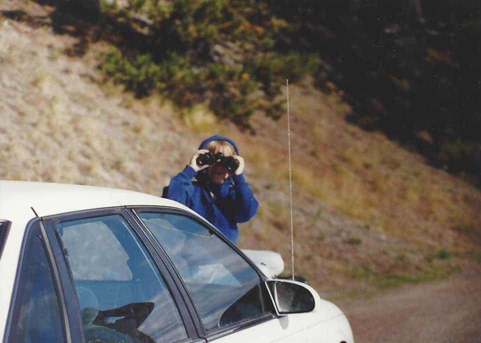Girl with binoculars near car at Yellowstone National Park: National Parks with kids