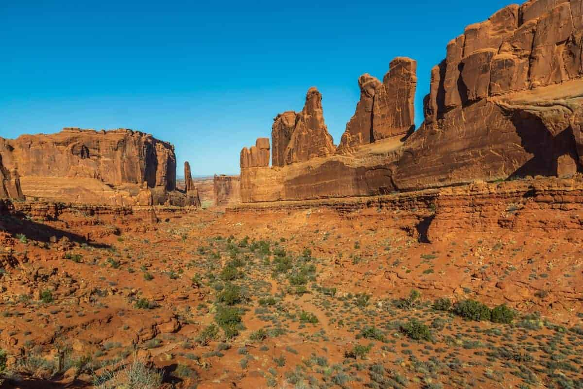The towering rock wall along the Park Avenue trail at Arches National Park.
