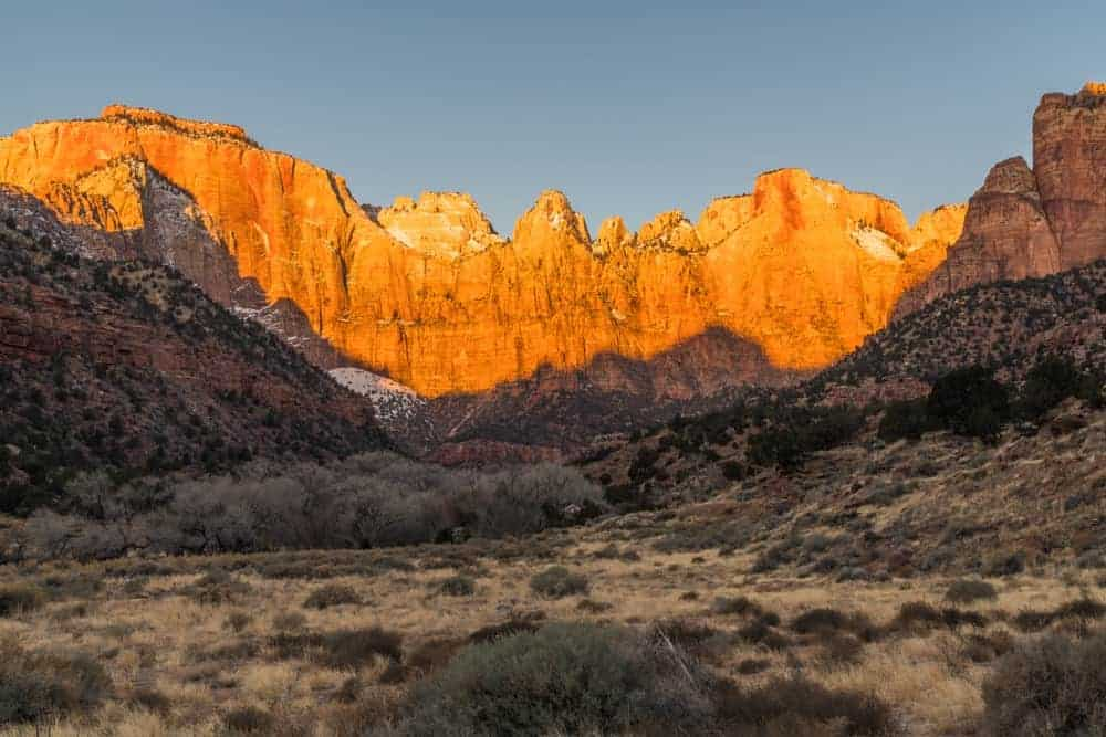 Sunrise light along the tops of the mountains that you'll see when visiting Zion National Park.