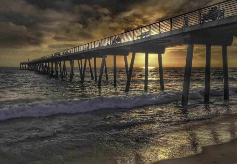 beach scene with pier at sunset