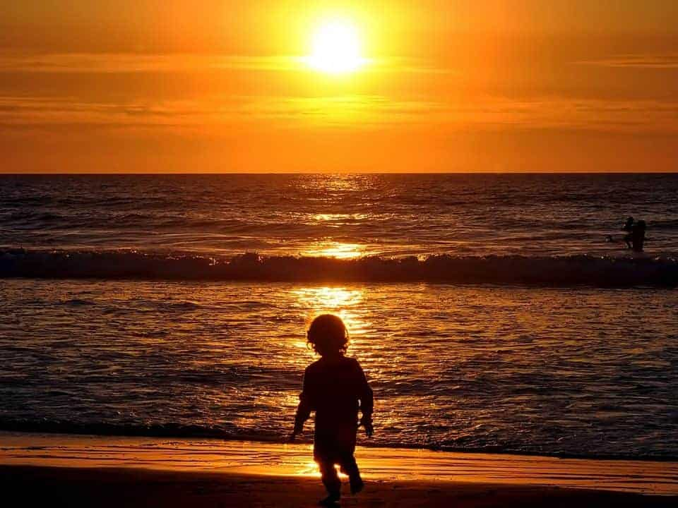 golden hour sunset with child on the beach