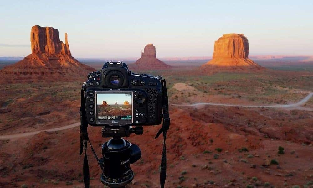 camera capturing sunset photo at Monument Valley